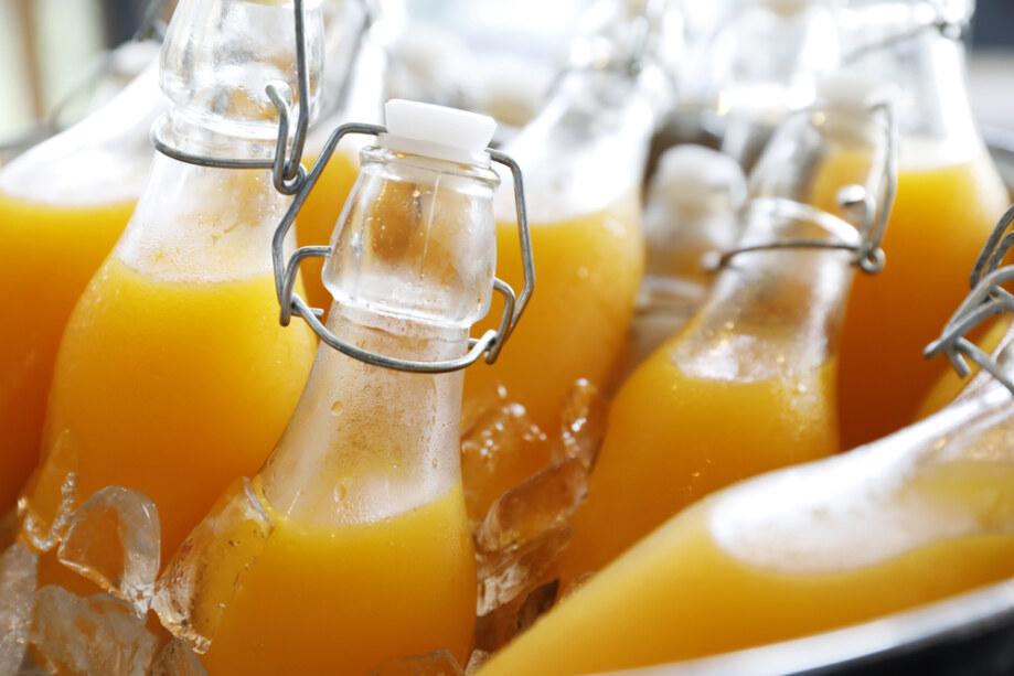 Closeup,Focus,Dept,Of,Field,Orange,Juice,Bottle,On,Ice