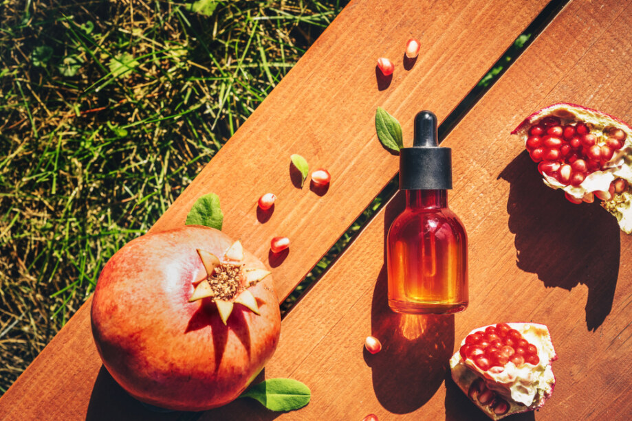 Pomegranate,Seed,Oil,,Serum,In,Glass,Bottle,On,Wooden,Background.